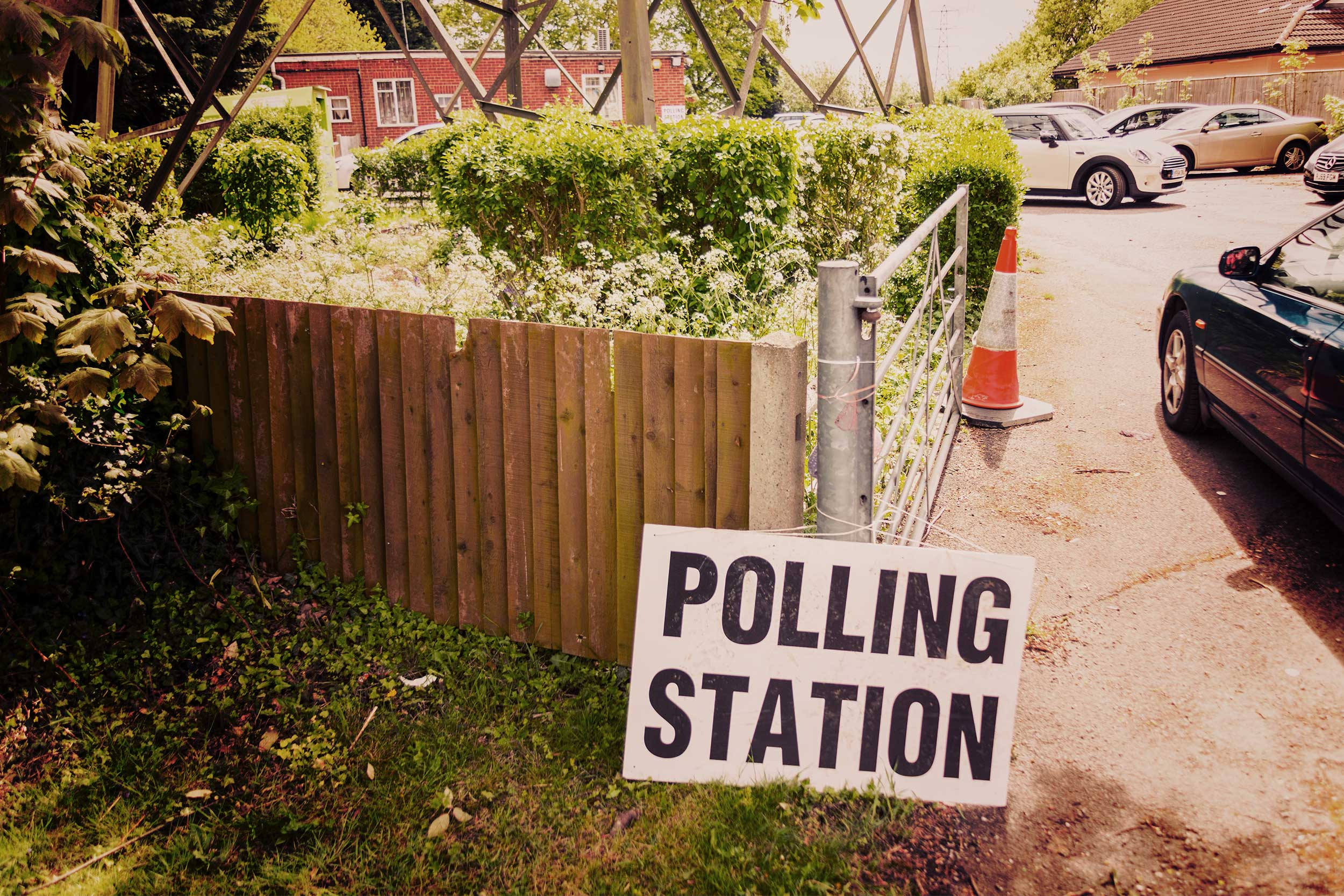 Image of a sign with 'Polling Station' printed on it propped against a garden fence.