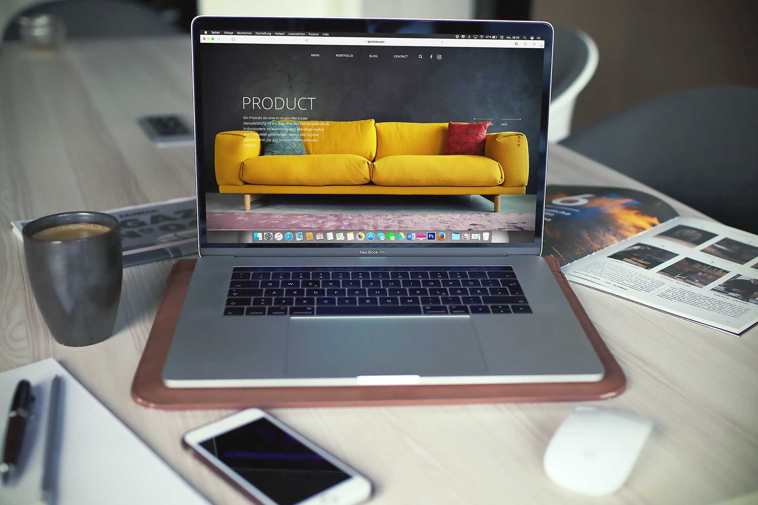 Image of a laptop on a busy desk showing an e-commerce storefront with a sofa on screen
