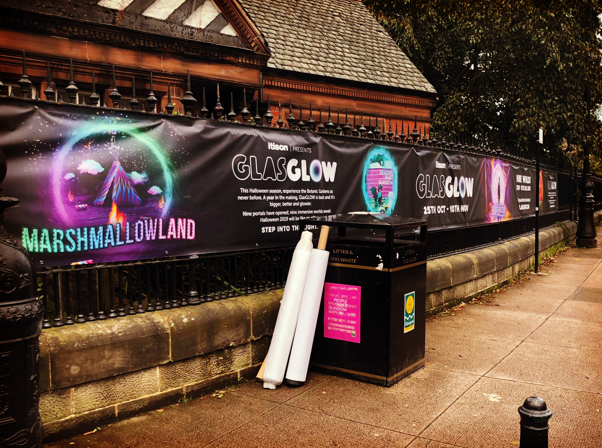 Image of a vinyl banner on an outdoor railing. Features a dark background and neon glow elements