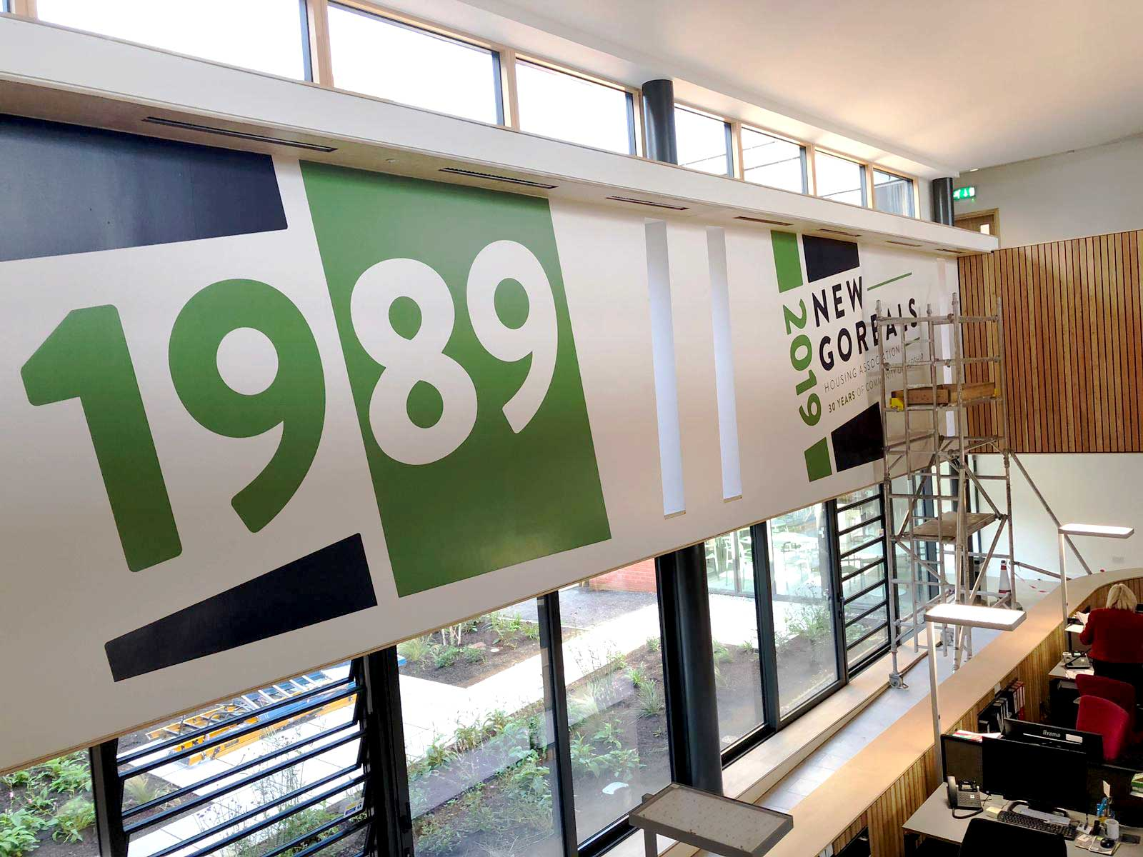 Image of a large format sign being fitted indoors and across large windows