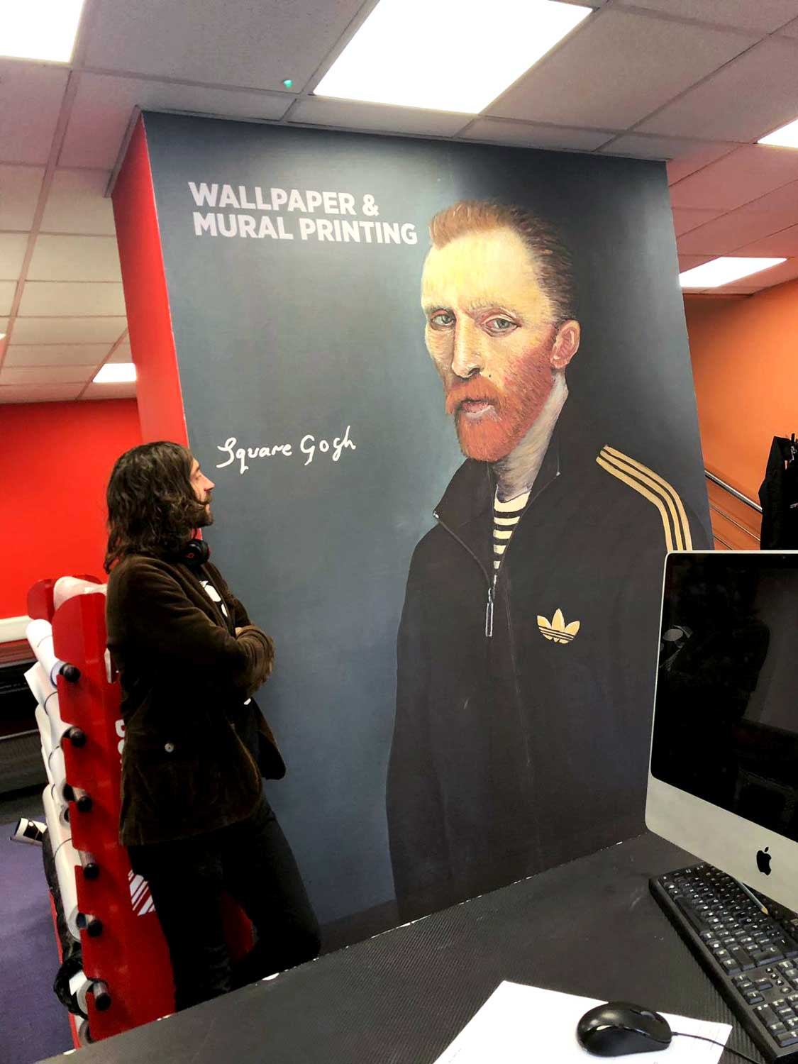 Local artist Ross Muir, standing next to a printed wall mural of one of his prints
