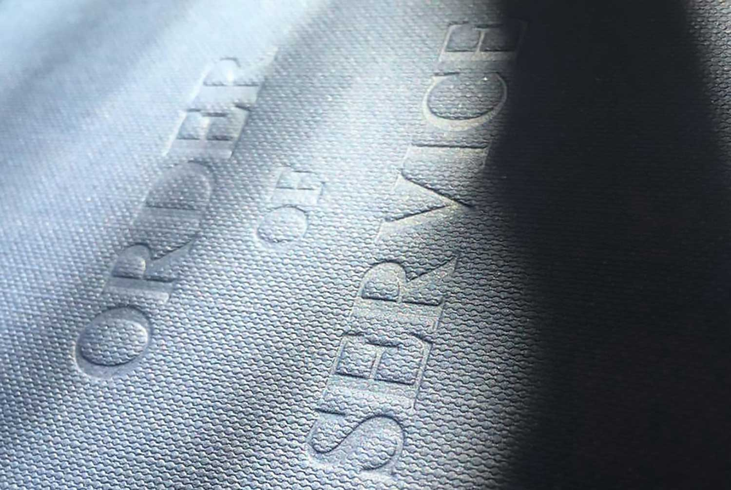 A particularly angled image of a letterpress order of service cover. WIth order of service embossed into the cover.